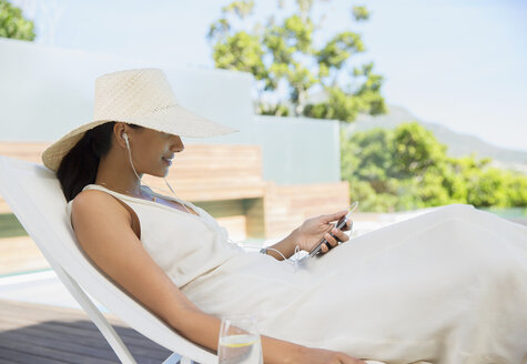 Woman listening to mp3 player outdoors - CAIF07817