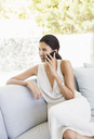 Woman talking on cell phone in livingroom - CAIF07850