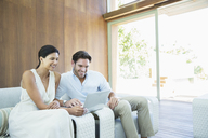 Couple using laptop on armchairs - CAIF07853