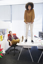 Business woman standing on table in office - CAIF07865
