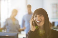 Businesswoman talking on cell phone in office - CAIF07874