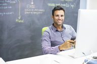 Businessman using cell phone at desk in office - CAIF07880