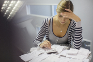 Frustrated woman paying bills - CAIF07910