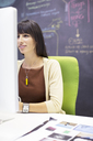 Businesswoman working at desk in office - CAIF07919
