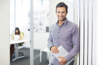Portrait of businessman smiling in office - CAIF07922