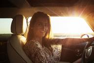 Portrait of happy woman sitting in car - CAVF01387