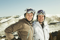 Portrait of happy couple in ski-wear standing against snowcapped mountain - CAVF01396