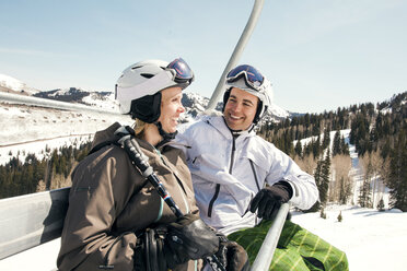 Happy couple sitting in ski lift against clear sky - CAVF01405