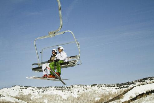 Skiers sitting in ski lift against clear sky - CAVF01408