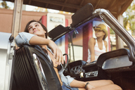 Woman sitting in car while friend standing at fuel pump - CAVF01432
