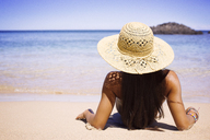 Rear view of woman relaxing at shore against sea - CAVF01447