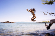 Woman jumping in sea against clear sky - CAVF01456