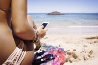 Cropped image of woman using phone while sitting at shore - CAVF01459