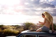 Friends sitting on car sunroof against sky - CAVF01471