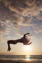 Woman backflipping against sky during sunset - CAVF01474
