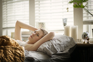 Woman looking away while lying on bed - CAVF01513