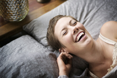 High angle view of woman laughing while lying on bed at home - CAVF01516