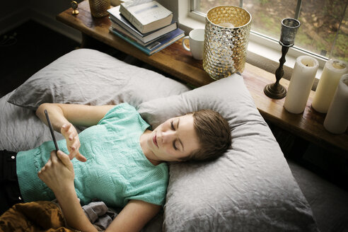 High angle view of woman using smart phone while lying on bed at home - CAVF01519