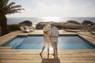 Senior couple hugging by modern pool overlooking ocean - CAIF07927