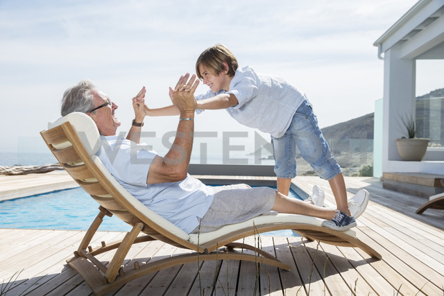 Grandfather and grandson playing at poolside - CAIF07933