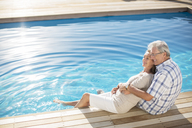 Senior couple relaxing by pool - CAIF07945