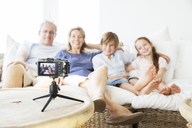 Family taking picture of themselves on sofa - CAIF07948