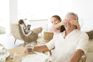 Girl covering grandfathers eyes - CAIF07951