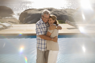 Older couple hugging by pool - CAIF07966