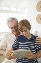 Older man and grandson using digital tablet - CAIF07975