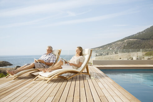 Older couple relaxing by pool - CAIF07978
