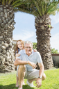 Older man and granddaughter smiling in backyard - CAIF07981