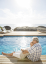 Older couple relaxing by pool - CAIF07984