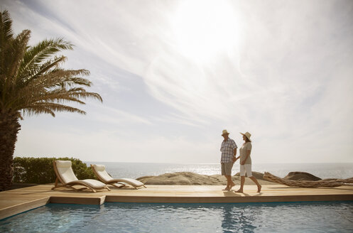 Older couple relaxing together by pool - CAIF07990