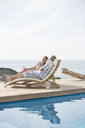 Older couple relaxing by pool - CAIF07993