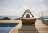 Older man reading by pool - CAIF07996