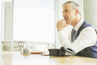 Businessman sitting at desk in office - CAIF08011