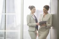 Businesswomen using digital tablet in office - CAIF08014