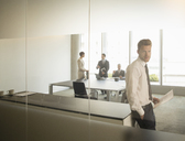 Businessman standing in office - CAIF08017
