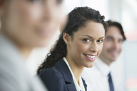 Businesswoman smiling in meeting - CAIF08035