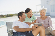 Family using digital tablet at poolside - CAIF08056
