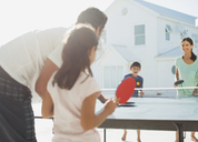 Family playing table tennis outside house - CAIF08059