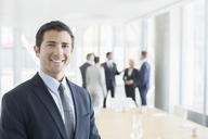 Businessman smiling in office - CAIF08080