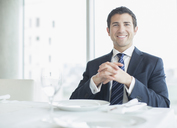 Businessman smiling in restaurant - CAIF08086