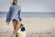 Rear view of woman walking on sand at beach - CAVF01570