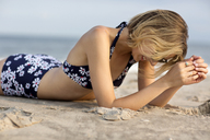 Side view of woman relaxing on sand at beach - CAVF01576
