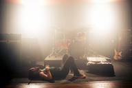Side view of man lying on floor in rock music studio - CAVF01585