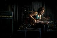 Musician practicing guitar in rock music studio - CAVF01588