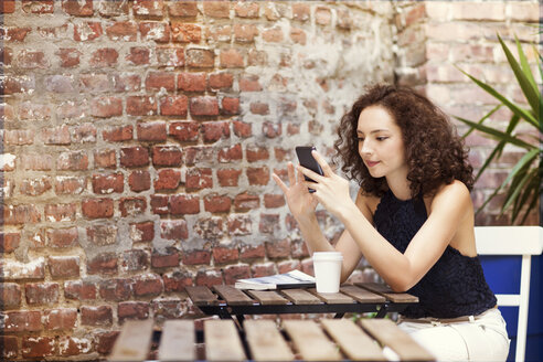 Woman using mobile phone while sitting in sidewalk cafe - CAVF01627