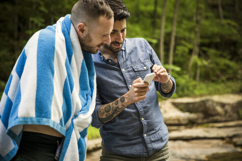 Man showing mobile phone to boyfriend while standing in forest - CAVF01666
