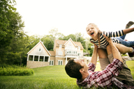 Playful man playing with daughter in backyard against sky - CAVF01684